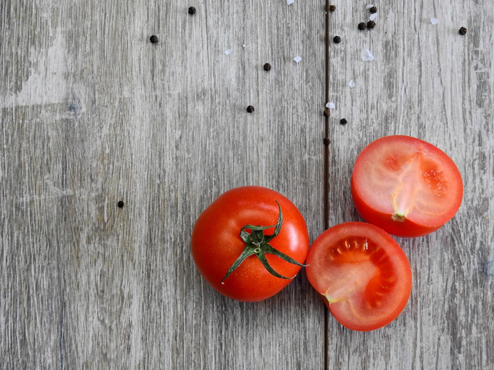 Two tomatoes on a wood background